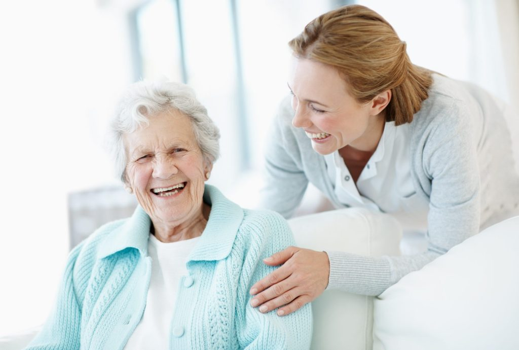 Elderly woman and caretaker share a laugh